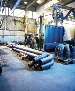 Steel pipes laying on protective blue flooring in metal shop