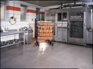 Meat processing facility displays rack of sausage resting over USDA approved flooring.
