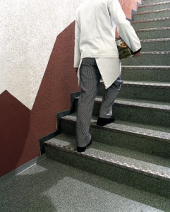 Man walking up stairs with dish on flooring system