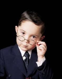 A boy dressed as an executive gives a judgmental look over rim framed glasses.