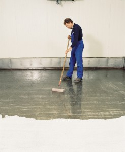 Man with roller in blue overalls paints flooring with acrylics.