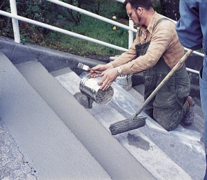 Two men paint gray acrylic on stairs leading from the floor above.