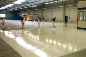 Contractors work diligently applying a concrete seal coating to a warehouse floor.