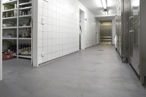 Laboratory hallway presents cool grey and white colors with its chemical resistant concrete flooring.