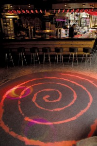 A dance floor ignites under the lights and sparkle of a clear acrylic floor sealer top coat.