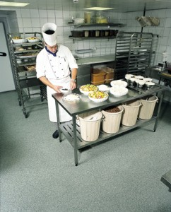 A chef preps the requirements atop a commercial kitchen flooring newly installed.