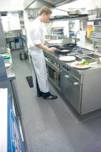 A commercial kitchen floor is depicted with chef prepping the requirements for the day.