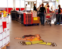 Floor graphic design in supermarket gives customers a bright reminder of the company logo.