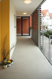 A concrete surface takes on the appearance of natural river rock in exterior hallway of commercial building.
