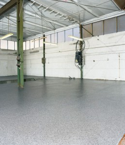 Industrial garage depicted displaying new concrete coating extending from garage to driveway.