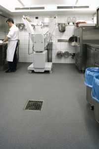 A working restaurant kitchen bustles with life over a newly installed seamless flooring system.