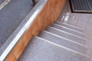 Stairs lead to a poured deck flooring system both displaying a beautiful grey white floor design.