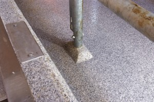 Close up view of a metal deck support surrounded by a poured deck flooring system.