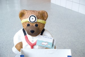 A small teddy bear rests atop new pharmaceutical flooring as a reminder of the importance of flooring protection.