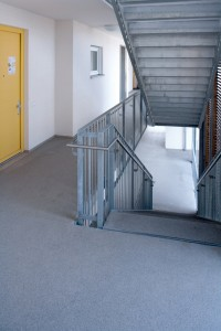 A new hallway floor covering system wraps around an interior flight of steps leading both up and down.