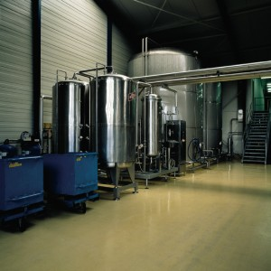 A thin overlay for cement floor system protects this factory floor from all manner of abuse.