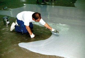 A flooring compound for self leveling is spread evening across a concrete floor by a certified installer.
