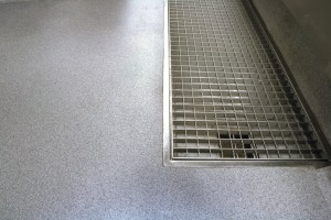 An institution flooring finish seamlessly surrounds this large floor drain.