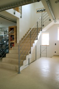Concrete staircases for industrial and commercial use require a poured floor system for superior protection such as this L shaped stairway.