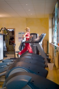 Woman jogs on row of treadmills covering this home gym floor space.