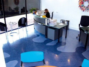 Industrial flooring ideas created this eclectic light and dark blue floor design located in an office foyer.