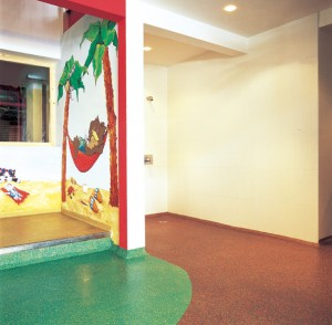 A multi colored rubber poured playground surface brightens this interior daycare play area.