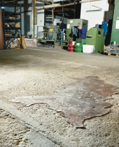 A badly damaged concrete floor is swept prior to the first coating of self leveling floor resin.