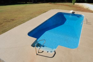A pool deck cement coating around a pool protects against the elements.