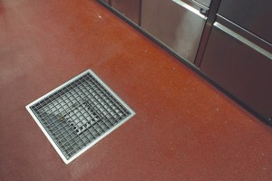 Flooring drains for sanitation protect this kitchen surface from any design of harm that may come from standing water, or spilled product.