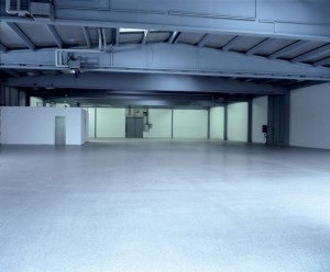 Large empty floor plan glows blue with specified poured hangar surface coating design.