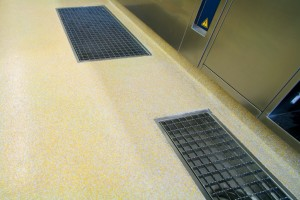 Finished yellow flooring seamlessly blends with two inset floor drain systems.