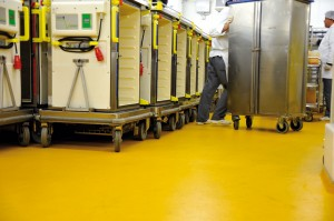Bright mustard yellow colored concrete floor system supports commercial rolling buggies.