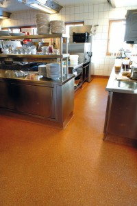 Deep orange colored flooring completes this seamless kitchen finish.