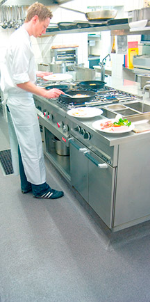 Chef Standing On Durable Flooring While Cooking In A Restaurant.