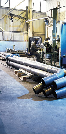 Large Pipes Laying On Strong Industrial Flooring While Man Welds In Background.