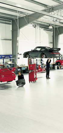 Mechanics Working On Cars Over Dense Industrial Floors.