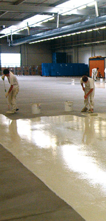 Men Installing Poured Flooring In A Large Warehouse.