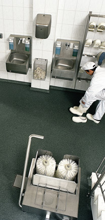Man Putting On Shoes In An Industrial Kitchen With Superior Flooring.