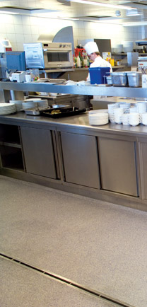 Flooring In Busy Franchise Kitchen That Enhances The All Metal Cabinets.