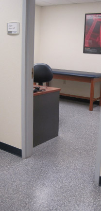 Exam Room With Table, Desk, And Hygienic Flooring.