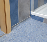 Shower entry flooring protected by an impregnated acrylic system.