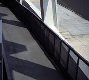 Exterior airport gateway casts shadows across seamless grey acrylic flooring system.