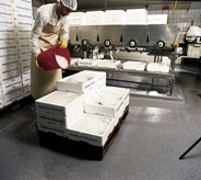 Worker ices down product while standing atop best water resist floor.
