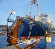 Large cargo boat loads boat floor covering supplies.