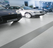 Cars atop multi colored large stripe flooring shine brightly in dealership.