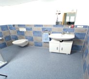 Quaint commercial setting extends into bathroom area flooring surrounded by matching checker board tiled walls.