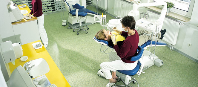 Dentist office with green flooring and a child in the dental chair having her teeth fixed.