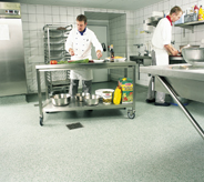 Grey coated flooring system covers concrete subsurface in commercial kitchen with prep cooks.