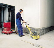 Professional flooring installer works large concrete resurfacing machine.