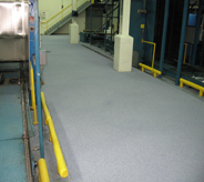Newly resurfaced concrete shines bright with grey coating in large industrial access walkway.